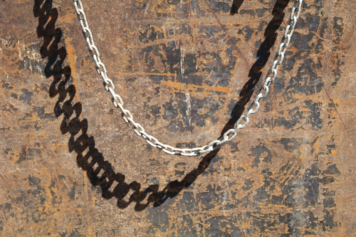 Chain and shadow against rusted metal at construction site in Houston, Texas